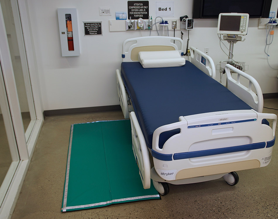 Hospital bed with custom foam mattress and floor mat.